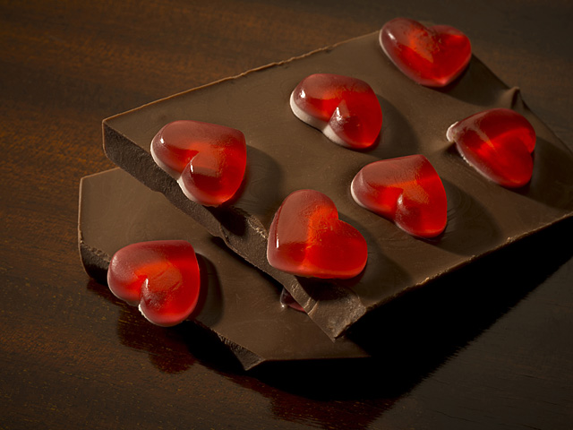 Red hearts stuck into milk chocolate bar
